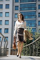 Businesswoman walking on bridge low angle view
