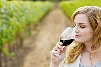 Young woman smelling red wine in vineyard
