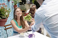 Man giving bunch of flowers to woman