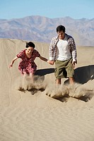 Couple sliding down on sand dune