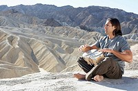 Man playing drums in desert, Death Valley, California, USA