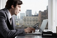 Businessman typing with laptop in office