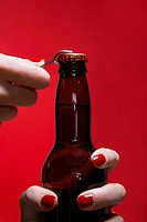 Young woman´s hands opening bottle of beer close_up