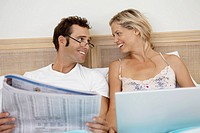 Mid adult couple using laptop and reading newspaper in bed