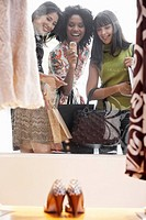 Three young women window shopping shoes
