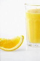 Slice of orange beside glass of orange juice