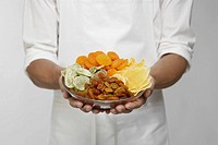 Selection of dried fruits on chef´s hands mid section