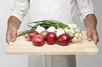 Chef holding cutting board with onions