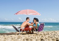 Multi_ethnic couple relaxing at beach