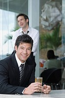 Hispanic businessman drinking cocktail