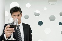 Hispanic businessman drinking wine