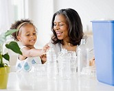 African grandmother teaching granddaughter how to recycle (thumbnail)