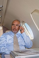 Hispanic businessman talking on cell phone in private jet