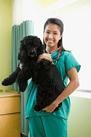 Eurasian veterinarian holding dog