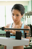 Eurasian woman weighing herself in health club