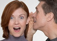 Man telling woman surprising secret