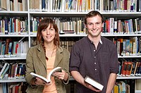 Portrait of two young people in library