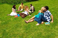Group of young people sitting on lawn