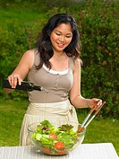 Young woman pouring olive oil on salad