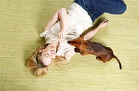 Young woman playing with dog (thumbnail)