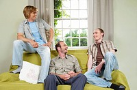 Three young men lounging on couch