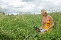 Woman sitting in field with laptop
