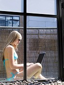 Woman sitting on balcony with laptop