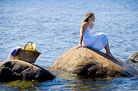 Girl in white dress on big rocks in the sea