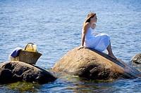 Girl in white dress on big rocks in the sea
