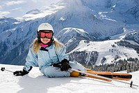 Girl with skis lying on the snow