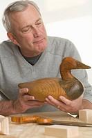 Man holding handmade wooden duck