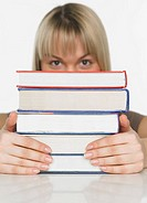 Studio shot of woman behind stack of books