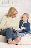 Grandmother reading to young granddaughter on sofa