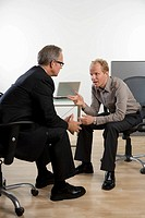 Two businessmen sitting and talking