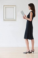 Woman in evening dress next to empty picture frame