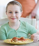 Girl eating spaghetti and meatballs