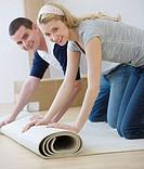 Couple unrolling rug