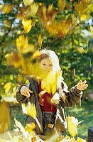 Girl catching autumn leaves