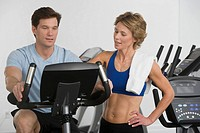 Personal trainer assisting man on stationary bike