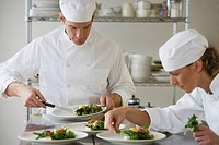 Male and female chefs plating food