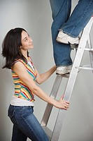Woman holding ladder while man climbs