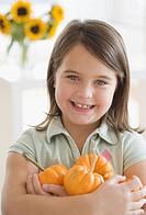 Portrait of girl holding pumpkins