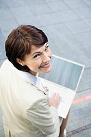 Germany, Baden Württemberg, Stuttgart, Business woman using laptop, smiling, portrait