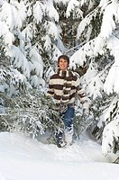 Austria, Salzburger Land, Altenmarkt, Young man carrying fir tree