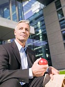 Germany, Baden_Württemberg, Stuttgart, Businessman holding an apple