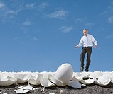 Mixed Race businessman walking on egg shells