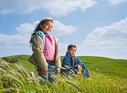 Hispanic children on grassy hillside