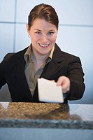 Customer service representative handing ticket over counter