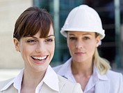 Germany, Baden_Württemberg, Stuttgart, Two businesswomen, one wearing hard hat, portrait
