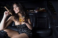 Glamorous woman smoking cigar in backseat of limousine
